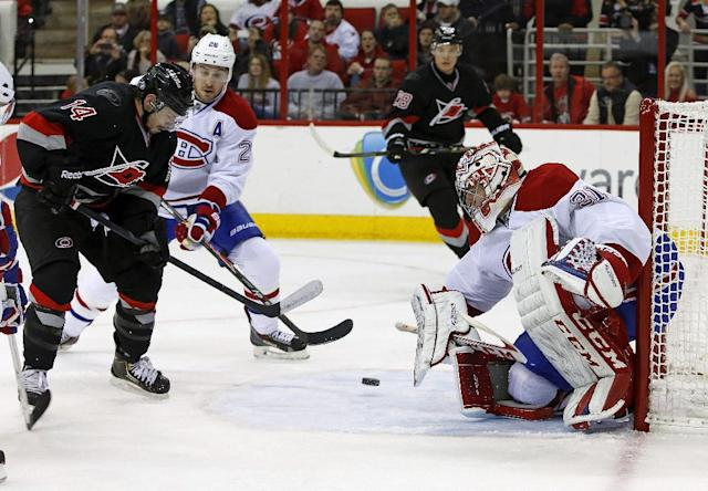 Carolina Hurricanes' Nathan Gerbe (14) tries to gather in the puck in front of Montreal Canadiens goalie Carey Price (31) as Canadiens' Josh Gorges (26) joins the play during the second period of an NHL hockey game in Raleigh, N.C., Tuesday, Dec. 31, 2013. (AP Photo/Karl B DeBlaker)