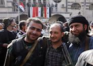 """In this Monday Feb. 17, 2014 photo, Syrian rebels, right, stands with two soldiers from Syrian government forces, center and left, as they pose for a picture after a reconciliation agreement between the two groups, in Babila, southeast Damascus, Syria. In one besieged neighborhood after another, weary rebels have turned over their weapons to the Syrian government in exchange for an easing of suffocating blockades that have prevented food, medicine and other staples from reaching civilians trapped inside. The government touts the truces as part of its program of """"national reconciliation"""" to end Syria's crisis, which has killed more than 140,000 people since March 2011. (AP Photo)"""