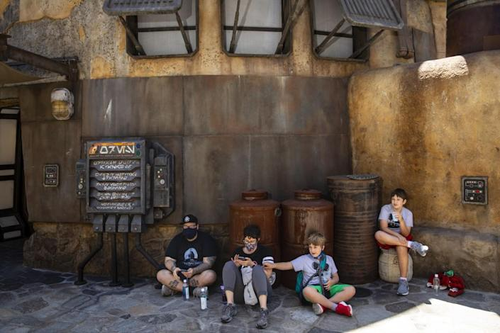 Four family members relax in the shade at Galaxy's Edge