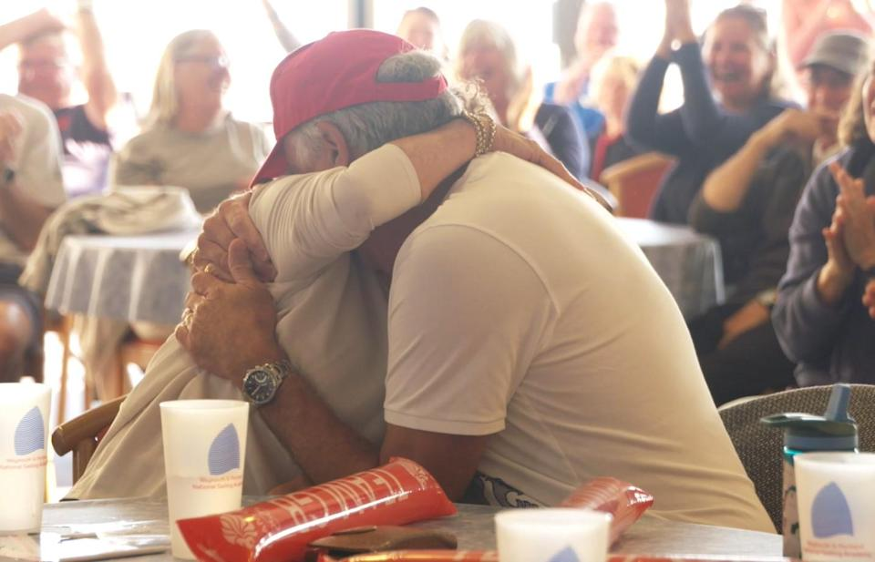 Ros and John Scott embraced as they watched their son secure victory (The Royal Yachting Association)