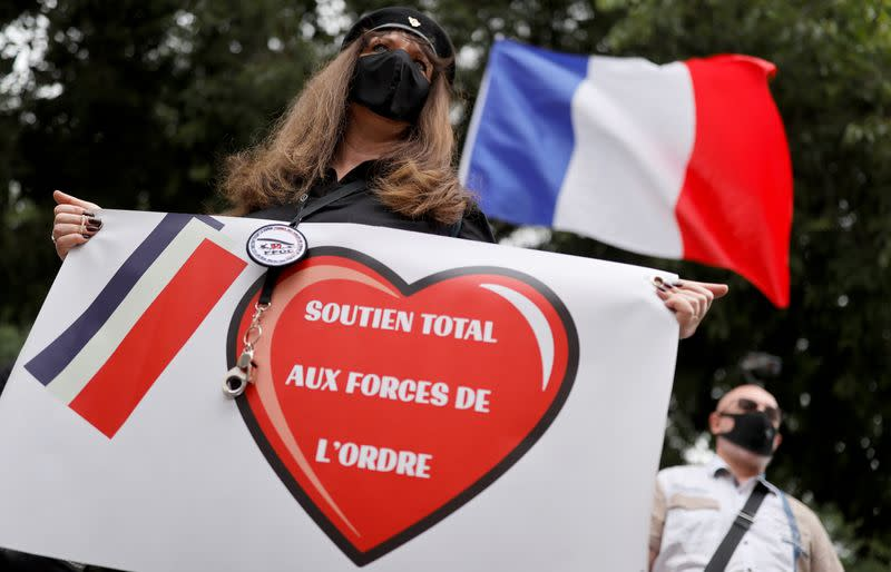 A supporter of police forces wearing a protective face mask holds a banner as she demonstrates in front of the French police headquarters in Paris