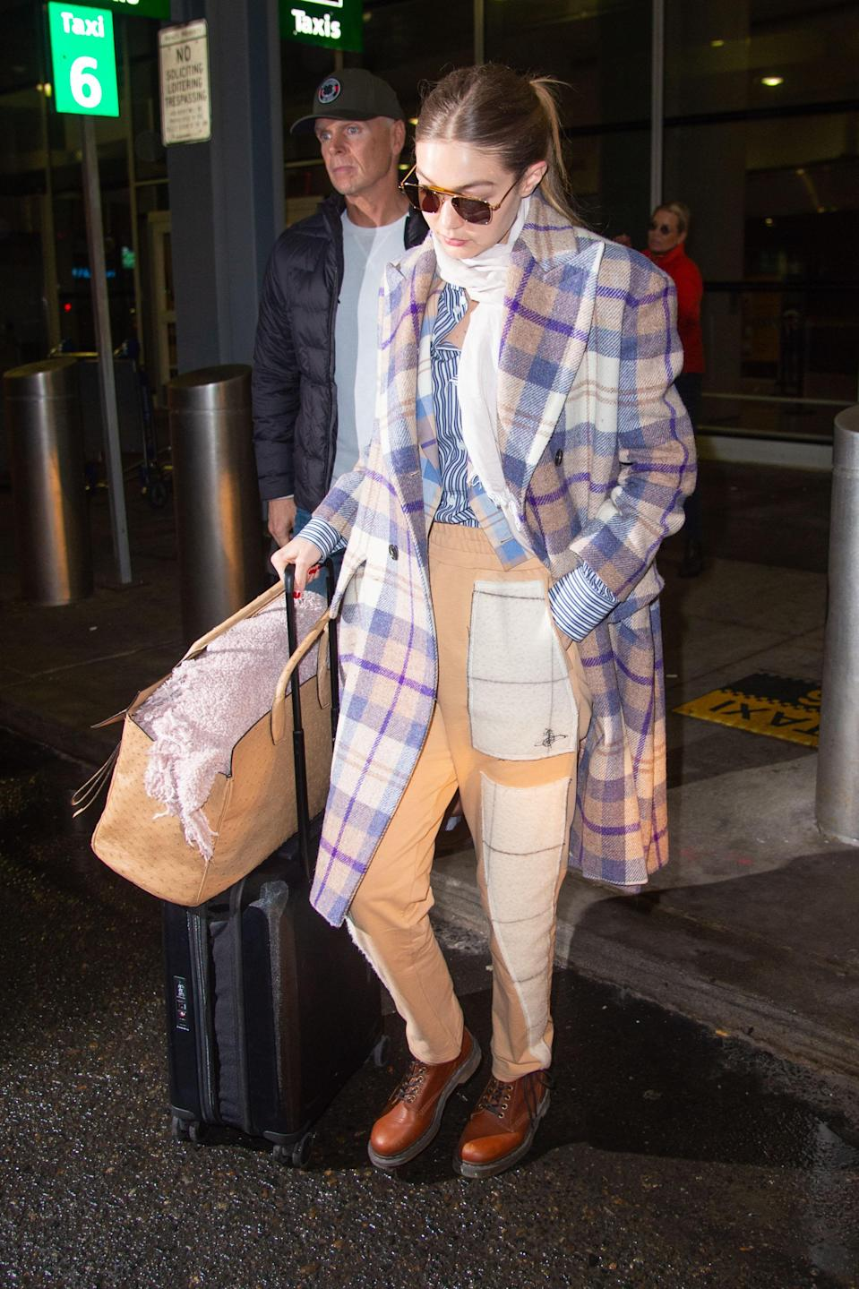 Gigi travels in style with the help of an oversized coat from Vivienne Westwood, an oversized bag from Salvatore Ferragamo, and, you guessed it, her go-to comfy Dr. Martens. Once you break your pair in, you'd not want to take them off either!