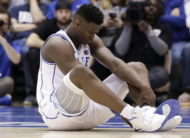 Duke's Zion Williamson sits on the floor following a injury during the first half of an NCAA college basketball game against North Carolina in Durham, N.C., Wednesday, Feb. 20, 2019. (AP Photo/Gerry Broome)