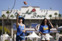 Gwyneth Schoenbaum, left, and Maddy Perdue play corn hole while tailgating outside of the Rose Bowl before an NCAA college football game between the Hawaii Warriors and the UCLA Bruins Saturday, Aug. 28, 2021, in Pasadena, Calif. Colleges across the country are cautiously optimistic that pregame tailgating will largely return to normal even since the emergence of the delta variant of the coronavirus. (AP Photo/Ashley Landis)