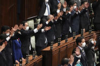 Japanese Prime Minister Fumio Kishida, forth from left, and other lawmakers give three cheers after dissolving the lower house, the more powerful of the two parliamentary chambers, during an extraordinary Diet session at the lower house of parliament Thursday, Oct. 14, 2021, in Tokyo. (AP Photo/Eugene Hoshiko)