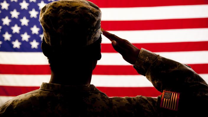 A member of the military salutes the American flag. (Getty Images)
