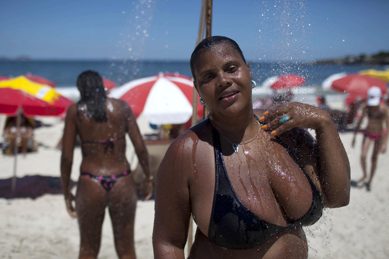 "In this photo taken on Jan. 25, 2012, Elisangela Inez Soares rinses off at a shower in Copacabana beach in Rio de Janeiro, Brazil. A growing number of bikini manufacturers have woken up to Brazil's thickening waistline and are reaching out to the ever-expanding ranks of heavy women with new plus-size lines. According to Soares "" not everyone is built like a model."" (AP Photo/Felipe Dana)"