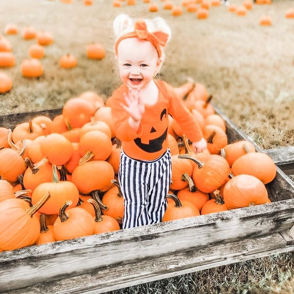 """""""I found the happiest, prettiest pumpkin in the patch—two years in a row!"""" <a href=""""https://www.instagram.com/p/B3Vdo59hEdr/"""">Mom wrote</a> of daughter Henley Grace's sweet shot."""