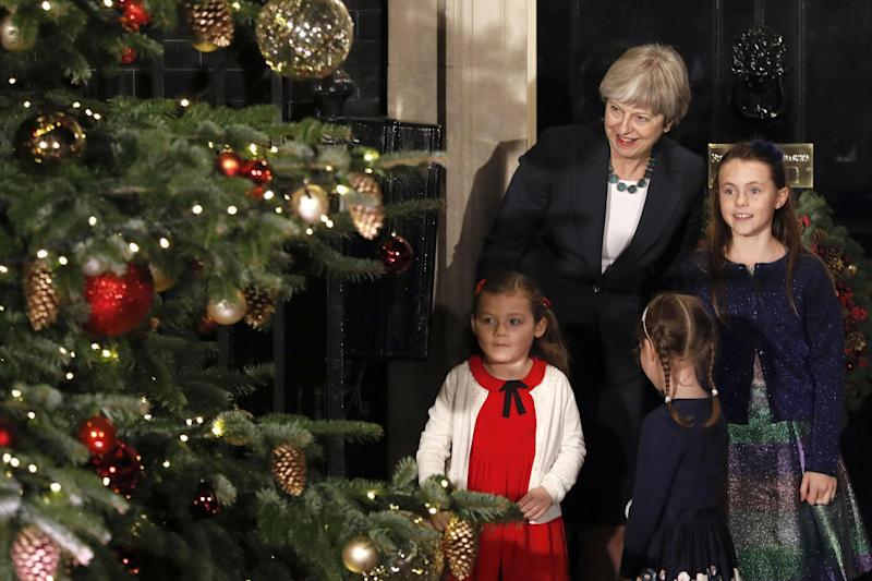 Theresa May stands with children as she switches on the Christmas tree lights: AP