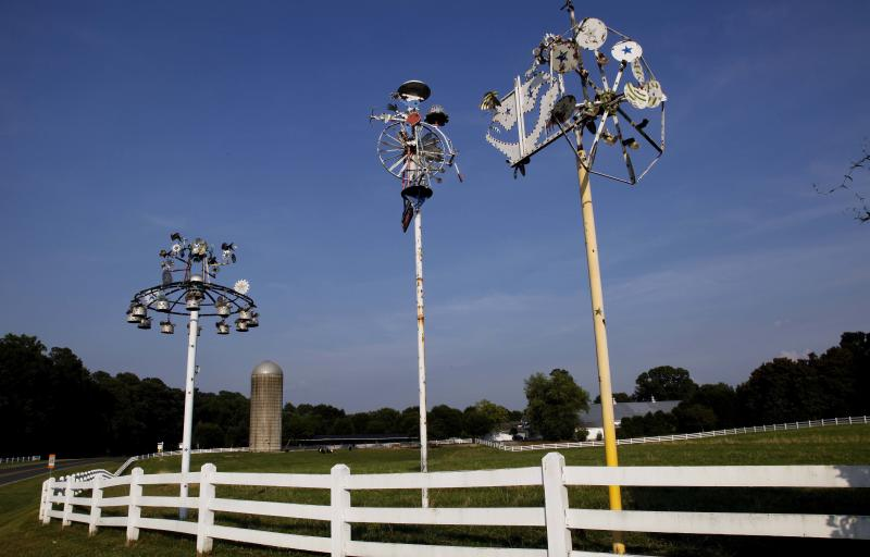 In this photo taken Monday, June 25, 2012, whirligigs by Vollis Simpson are shown along the entrance to Fearrington Village near Pittsboro, N.C. In a huge warehouse a few miles from where Simpson's whirligigs have stood for years in Lucama, N.C., people spend their days repairing the wind-driven creations, giving them the same attention that one gives a Picasso. They're repairing the whirligigs in advance of moving them next year to a downtown park. (AP Photo/Gerry Broome)