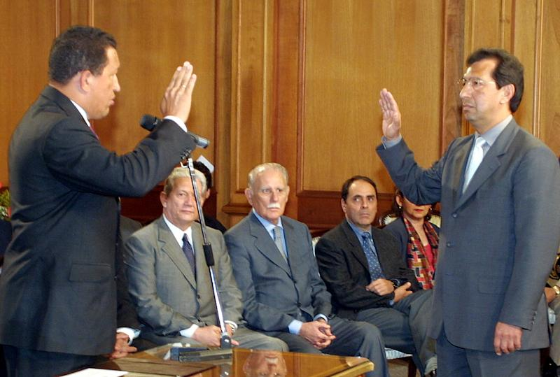 FILE - In this Jan. 9, 2002 file photo, Venezuela's President Hugo Chavez, left, swears in his older brother Adan Chavez as head of National Institute of Land and Agricultural Development at Miraflores presidential palace in Caracas, Venezuela.  Chavez's precarious health appears to be prompting him to look into his inner circle for those he thinks are most capable of managing his socialist revolution while he undergoes cancer treatment. Possible candidates include his elder brother, Adan, who is currently governor in Chavez's home state of Barinas. Those standing out also include Chavez's foreign minister, his energy minister and a few trusted military officers, both current and former. Yet if Chavez has his mind set on any particular heir to power, he hasn't yet sent clear signals as to whom it would be.   (AP Photo/Juan Carlos Solorzano, Miraflores, File)