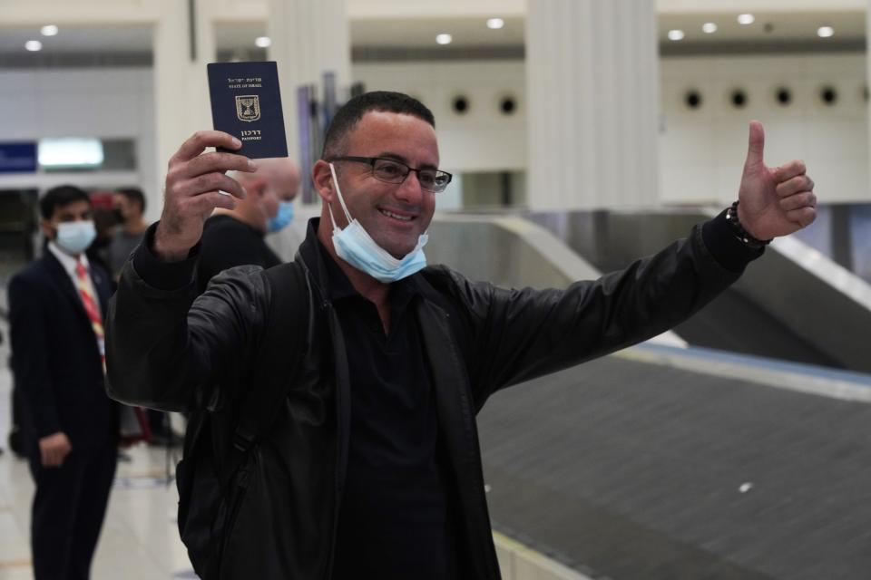 An Israeli passenger from a flyDubai flight from Tel Aviv, Israel, waves his Israeli passport on arrival at Dubai International Airport's Terminal 3 in Dubai, United Arab Emirates, Thursday, Nov. 26, 2020. The low-cost carrier flyDubai began regular flights to Tel Aviv on Thursday, the latest sign of the normalization deal between the UAE and Israel. (AP Photo/Jon Gambrell)