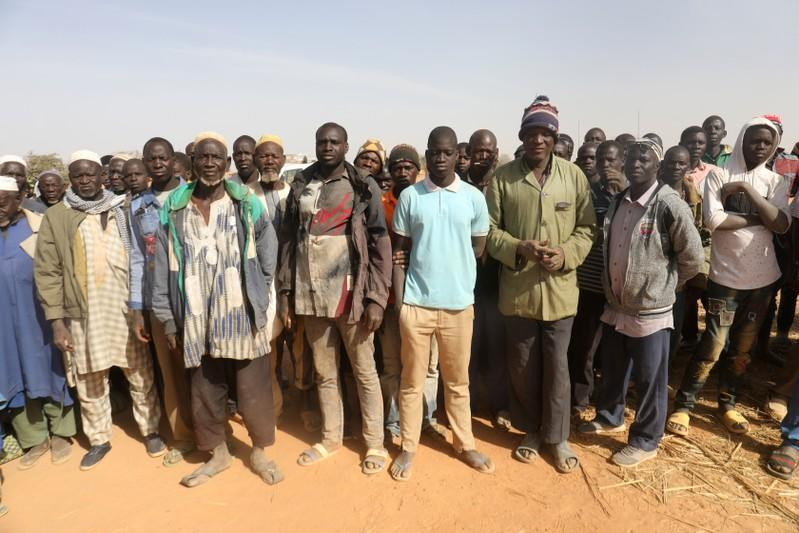 Displaced people wait for help at a village in Dablo area