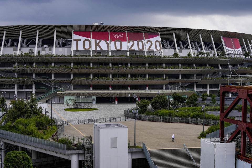 A worker walks through the front entrance of National Stadium Wednesday, June 23, 2021, in Tokyo, one month before the July 23 opening of Tokyo Olympics. The Tokyo Olympics, already delayed by the pandemic, are not looking like much fun: Not for athletes. Not for fans. And not for the Japanese public. They are caught between concerns about the coronavirus at a time when few are vaccinated on one side and politicians who hope to save face by holding the games and the International Olympic Committee with billions of dollars on the line on the other. (AP Photo/Kiichiro Sato)