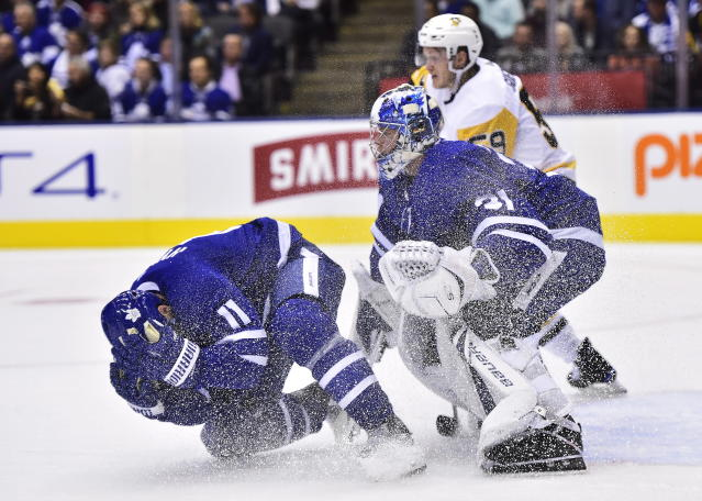 Toronto Maple Leafs centre Zach Hyman (11) falls to the ice as goalie Frederik Andersen and Pittsburgh Penguins centre Jake Guentzel (59) look on during first period NHL hockey action in Toronto on Thursday, Oct. 18, 2018. (Frank Gunn/The Canadian Press via AP)