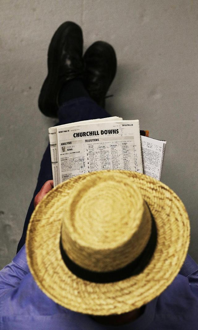 A man looks over a racing form before the 140th running of the Kentucky Derby horse race at Churchill Downs Saturday, May 3, 2014, in Louisville, Ky. (AP Photo/Charlie Riedel)