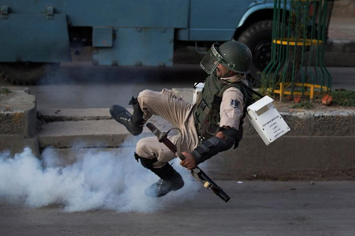 <p>AUG. 8, 2016 — An Indian paramilitary soldier falls down as he tries to kick back an exploded tear gas shell thrown back at them by Kashmiri Muslim protesters at the end of a day long curfew in Srinagar, Indian controlled Kashmir. Kashmir has been under a security lockdown and curfew since the killing of a popular rebel commander on July 8 sparked some of the largest protests against Indian rule in recent years. (Dar Yasin/AP) </p>