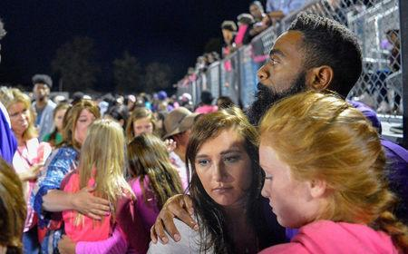 Olympic sprinter Tyson Gay embraces those gathered during a candlelight vigil at Lafayette High School for his daughter Trinity Gay, who died in an exchange of gunfire early Sunday morning, in Lexington, Kentucky, October 17, 2016. REUTERS/Bryan Woolston