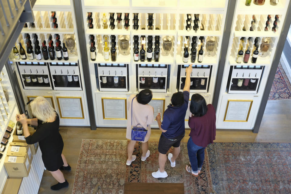 A group of people look to select wines from a dispensary at the Oakville Wine Merchant Friday, June 12, 2020, in Oakville, Calif. California wineries started uncorking their bottles and welcoming people back to their tasting rooms Friday as the state's $145 billion tourism industry gears up with hotels, zoos, museums and aquariums also allowed to reopen. The wine retail experience in Oakville features 50 different wines by the taste or glass and is open to the public without an appointment. (AP Photo/Eric Risberg)