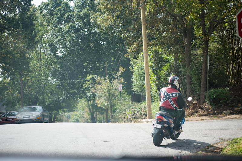 A person wearing a jacket decorated with a Confederate flag passes by on a moped in Asheville.