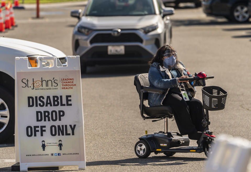Veronica Lopez, who has Spina bifida, arrives for her vaccine appointment at the St. John's Well Child and Family Center's COVID-19 vaccination site at the East Los Angeles Civic Center in Los Angeles, Thursday, March 4, 2021. California will begin setting aside 40% of all vaccine doses for the state's most vulnerable neighborhoods in an effort to inoculate people most at risk from the coronavirus more quickly. (AP Photo/Damian Dovarganes)