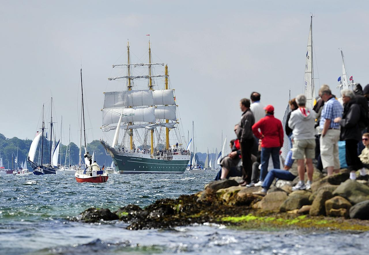 """KIEL, GERMANY - JUNE 23:  Visitors watch the """"Alexander von Humboldt II"""" tall ship at the Windjammer Parade of tall ships on June 23, 2012 in Kiel, Germany. The parade, which features approximately 100 tall ships and traditional large sailing ships, is the highlight of the Kieler Woche annual sailing festival, which this year is celebrating its 130th anniversary and runs from June 16-24.  (Photo by Patrick Lux/Getty Images)"""