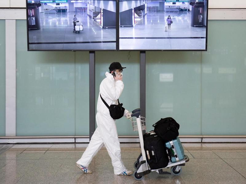A passenger wearing protective gear, as a precautionary measure against coronavirus, walks in the arrivals area after landing at the Hong Kong International Airport: AFP/Getty
