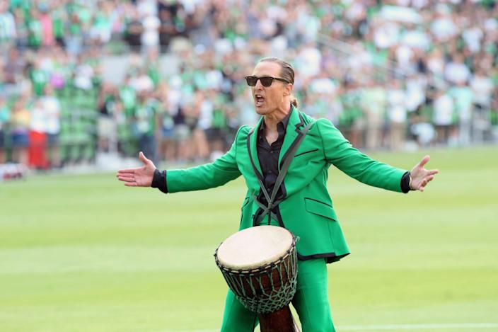 Matthew McConaughey in a green suit with a drum between his legs