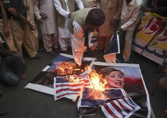 A supporter of religious political party Sunni Tehreek set ablaze the images of U.S. President Barack Obama (L), U.S. Secretary of State Hillary Clinton (R), the NATO and the U.S. flags during a demonstration in Karachi December 1, 2011. Pakistan, enraged by a NATO cross-border air attack that killed 24 soldiers, could withdraw its support for the U.S.-led war on militancy if its sovereignty is violated again, the foreign minister suggested in comments published.