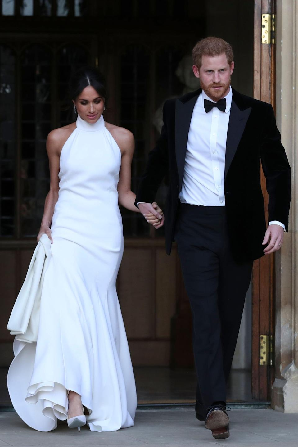 """<p>While we will never forget <a href=""""https://www.popsugar.com/fashion/Meghan-Markle-Wedding-Dress-44842704"""" class=""""link rapid-noclick-resp"""" rel=""""nofollow noopener"""" target=""""_blank"""" data-ylk=""""slk:Meghan's Givenchy three-quarter-sleeved satin wedding dress"""">Meghan's Givenchy three-quarter-sleeved satin wedding dress</a>, created by Clare Waight Keller, it was <a href=""""https://www.popsugar.com/fashion/Meghan-Markle-Second-Wedding-Dress-44757685"""" class=""""link rapid-noclick-resp"""" rel=""""nofollow noopener"""" target=""""_blank"""" data-ylk=""""slk:her Stella McCartney reception gown"""">her Stella McCartney reception gown</a> that really stole the show and made headlines. The Duchess of Sussex styled her bespoke halter-neck number with Aquazzura heels and <a href=""""https://www.popsugar.com/fashion/Meghan-Markle-Blue-Ring-Her-Wedding-2018-44862617"""" class=""""link rapid-noclick-resp"""" rel=""""nofollow noopener"""" target=""""_blank"""" data-ylk=""""slk:Princess Diana's Asprey gemstone ring"""">Princess Diana's Asprey gemstone ring</a> when she joined Prince Harry for their party at Frogmore House on the evening of May 19. Meghan's decision to show off some skin and bare her shoulders will forever go down in history as a significant moment in royal dressing.</p>"""