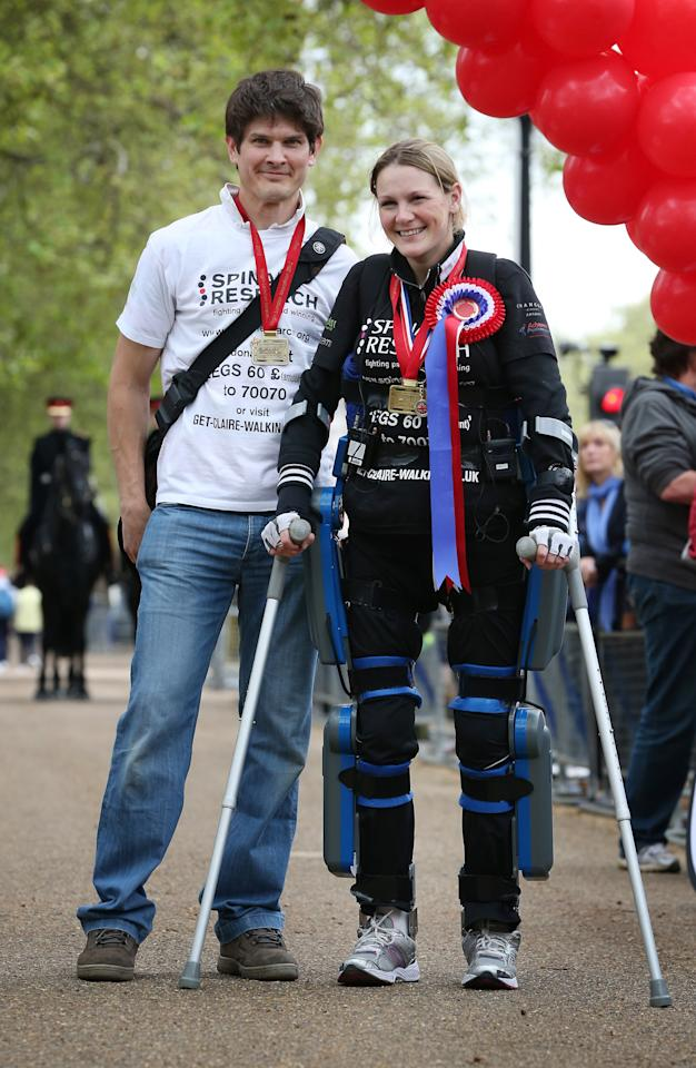LONDON, ENGLAND - MAY 08:  Claire Lomas stands with her husband Dan Spincer after crossing the finishing line of the Virgin London Marathon on May 8, 2012 in London, England. Ms Lomas, who is paralysed from the waist down after a riding accident in 2007, has taken 16 days to complete the 26.2 mile route. Starting out with 36,000 other runners she has averaged 2 miles a day with the help of a bionic ReWalk suit.  (Photo by Peter Macdiarmid/Getty Images)
