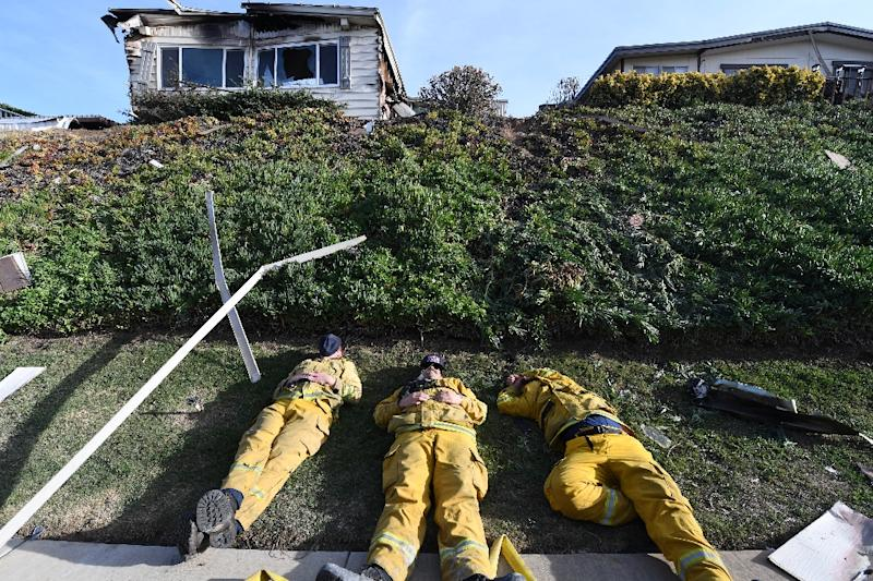 Exhausted firefighters have their first rest in over 20 hours since starting to fight the Lilac Fire, December 8, 2017, in Bonsall, California (AFP Photo/Robyn Beck)