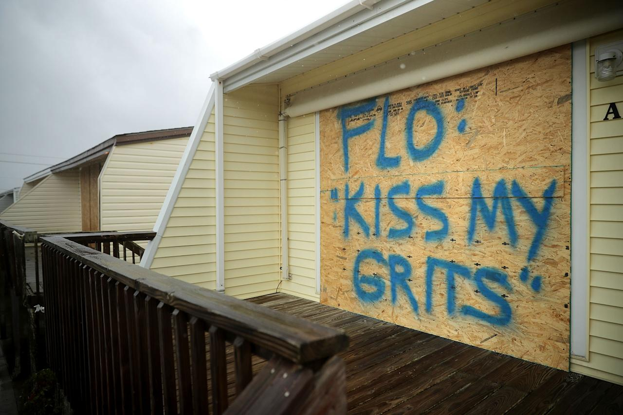 <p>A spray painted message is left on a boarded up condominium as the outer bands of Hurricane Florence being to affect the coast on Sept. 13, 2018 in Atlantic Beach, United States. (Photo: Chip Somodevilla/Getty Images) </p>