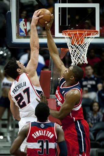 Washington Wizards' Kevin Seraphin (13) blocks a shot by Atlanta Hawks' Zaza Pachulia during the first half of an NBA basketball game in Atlanta, Friday, March 16, 2012. (AP Photo/Rich Addicks)