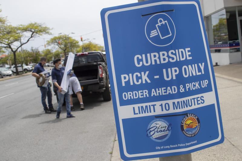 A reserved parking for curb-side pick-up sign is seen, Wednesday, May 27, 2020, in Long Beach, N.Y. Long Island has become the latest region of New York to begin easing restrictions put in place to curb the spread of the coronavirus as it enters the first phase of the state's four-step reopening process. (AP Photo/Mary Altaffer)