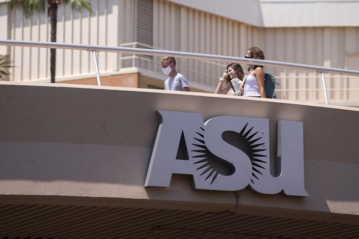 Students walk across the bridge above University Drive the day before school opens on Aug. 19, 2020, at Arizona State University in Tempe.