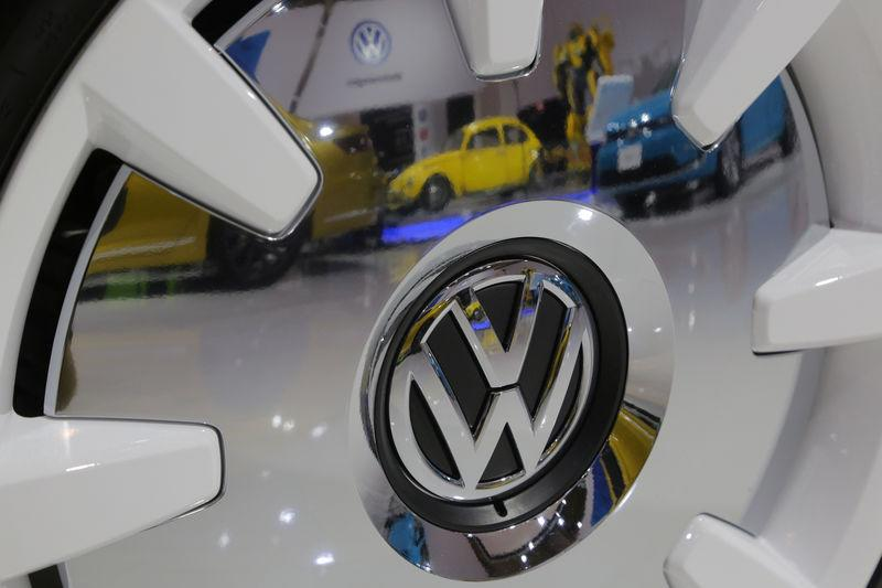 A Volkswagen Beetle is reflected in the chrome of a wheel at the Canadian International AutoShow in Toronto