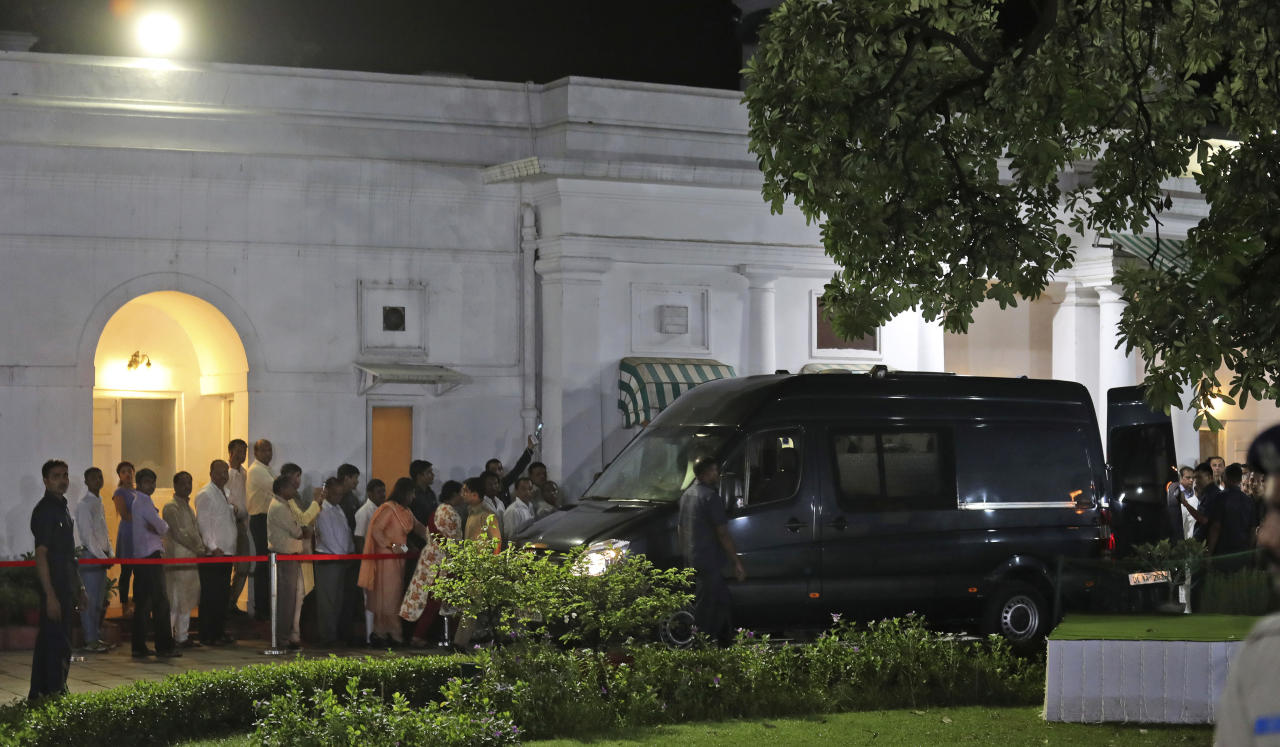 An ambulance carrying the body of former Indian prime minister Atal Bihari Vajpayee arrives at his residence in New Delhi, India, Thursday, Aug. 16, 2018. Vajpayee, a Hindu nationalist who set off a nuclear arms race with rival Pakistan but later reached across the border to begin a groundbreaking peace process, died on Thursday after a prolonged illness. He was 93. (AP Photo/Manish Swarup)