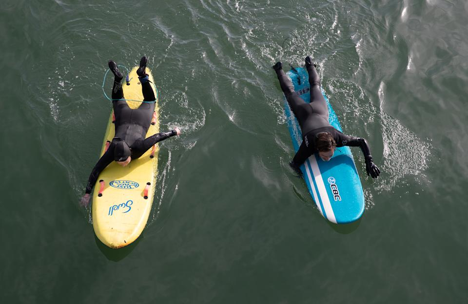 Two paddle boarders in the sea off of Boscombe beach in Dorset. Picture date: Tuesday March 30, 2021. Temperatures in parts of the UK are expected to be significantly warmer this week as families and friends are reunited and sporting activities are allowed to resume in England.