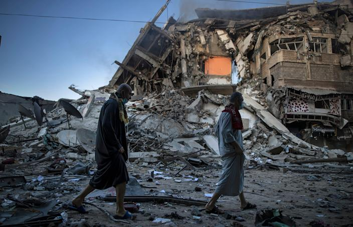 May 13, 2021: Palestinians walk next to the remains of a destroyed 15 story building after being hit by Israeli airstrikes on Gaza City.