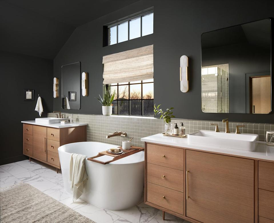 <p>Chip and Joanna replaced the closets with two single-sink vanities, painted both the walls and ceilings with the same dark green they used in the kitchen, added a bathtub, and installed white-marbled porcelain flooring.</p>