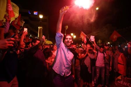 Supporters of Tunisian presidential candidate Kais Saied celebrate after unofficial results of the second round runoff of a presidential election in Tunis