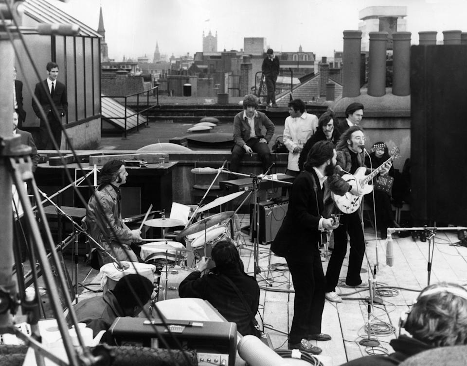 30th January 1969:  British rock group the Beatles performing their last live public concert on the rooftop of the Apple Organization building for director Michael Lindsey-Hogg's film documentary, 'Let It Be,' on Savile Row, London, England. Drummer Ringo Starr sits behind his kit. Singer/songwriters Paul McCartney and John Lennon perform at their microphones, and guitarist George Harrison (1943 - 2001) stands behind them. Lennon's wife Yoko Ono sits at right.  (Photo by Express/Express/Getty Images)