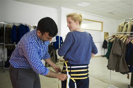 Moses, co-founder of clothes sizing software start-up UPCload, demonstrates a customised pair of trousers used to take body measurements at the UPCload office in Berlin