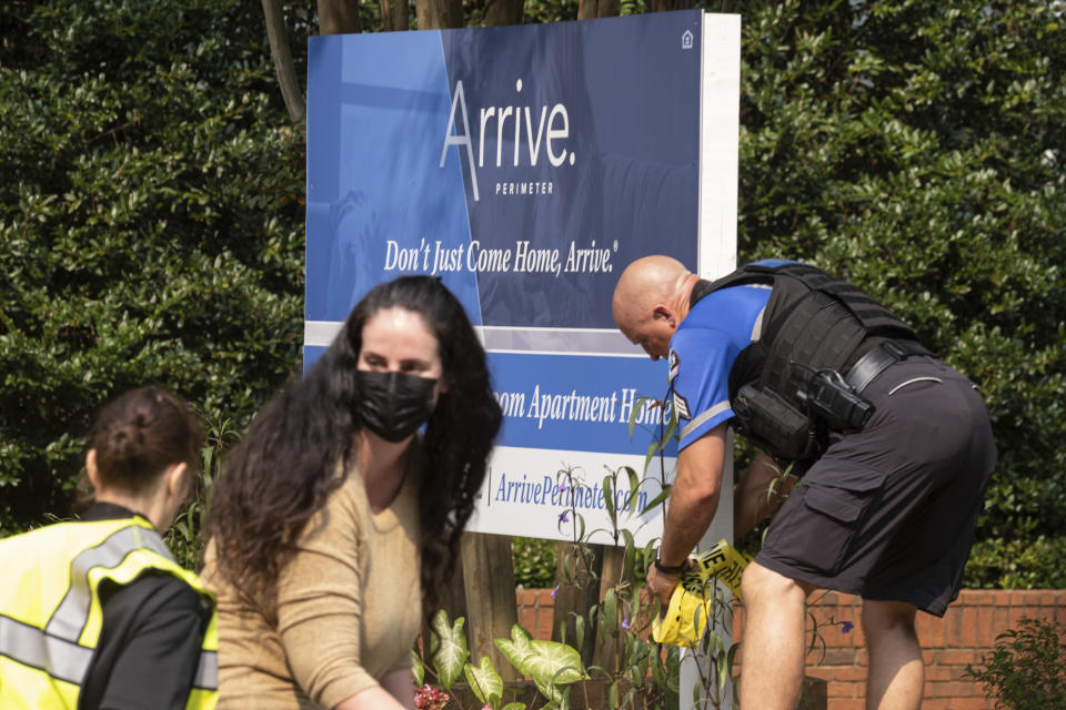 A police officer ties caution tape to the Arrive Perimeter apartment complex sign following an explosion at the complex, Sunday, Sept. 12, 2021, in Dunwoody, Ga., just outside of Atlanta. (AP Photo/Ben Gray)