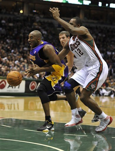 Los Angeles Lakers' Kobe Bryant left, drives to the basket against the Milwaukee Bucks' Luc Richard Mbah a Moute (12) during the first half of an NBA basketball game on Saturday, Jan. 28, 2012, in Milwaukee. (AP Photo/Jim Prisching)