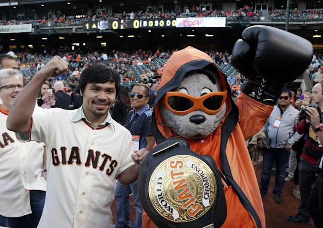 Boxer Manny Pacquiao, left, poses for pictures with San Francisco Giants mascot Lou Seal before Pacquiao was to throw the ceremonial first pitch before a baseball game between the Giants and Milwaukee Brewers on Friday, Aug. 29, 2014, in San Francisco. (AP Photo/Marcio Jose Sanchez)
