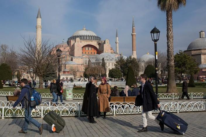 """Tourists walk past the Hagia Sophia in Istanbul, Turkey, in a photo taken before the COVID-19 pandemic. <span class=""""copyright"""">(Chris McGrath / Getty Images)</span>"""