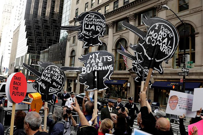 <p>Demonstrators hold up signs while marching past Trump Tower as they call on President Donald Trump to release his tax returns, April 15, 2017, in New York. (Photo: Lucas Jackson/Reuters) </p>