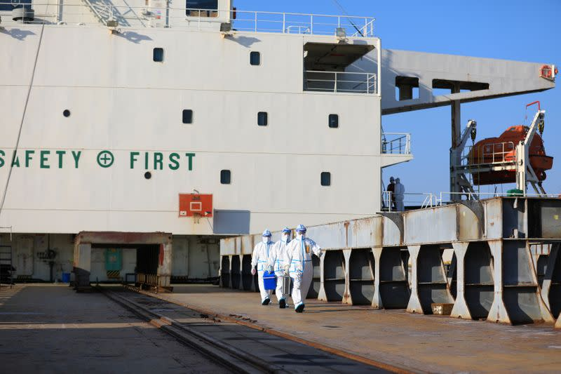 Customs officers in protective suits leave a ship following an inspection at a shipyard in Rongcheng
